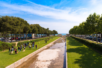 CAMBRILS, SPAIN - APRIL 30, 2017: A group of people walking in a park with dogs. Top view.
