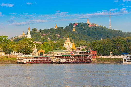 MANDALAY, MYANMAR - DECEMBER 1, 2016: Sagaing city port. Golden pagodas, Burma. Copy space for text.