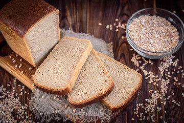A loaf of rye bran bread with slices on sackcloth on cutting board and wheat on dark wooden background.