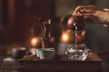 Female hands pouring tea from a teapot