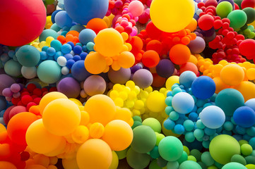 Bright abstract background of jumble of rainbow colored balloons celebrating gay pride