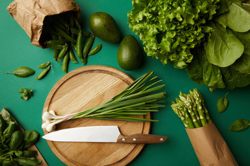 top view of different ripe vegetables with wooden cutting board and knife on green surface Wall mural