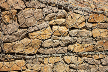 Stone wall in a metal grid as a background