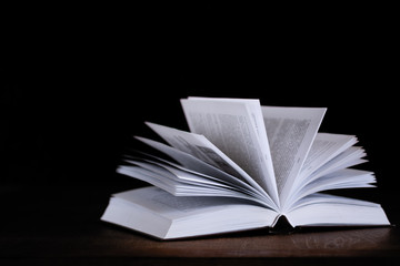 open book lying on a table on a dark background