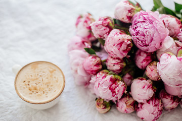 Cup of coffee and a bouquet of peonies.