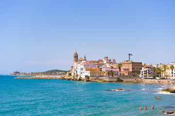SITGES, CATALUNYA, SPAIN - JUNE 20, 2017: View of the historical center and the ñhurch of Sant Bartomeu and Santa Tecla. Copy space for text. Isolated on blue background.