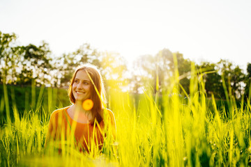 Young woman sitting laughing in the grass in the sunshine