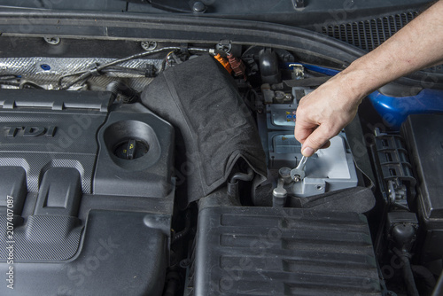 Repairman With Wrench Checking Car Battery Contacts