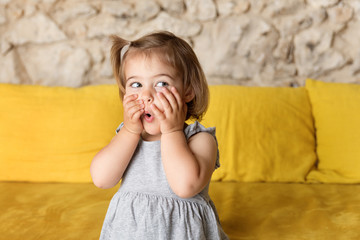 Little girl making funny suprised face on yellow couch