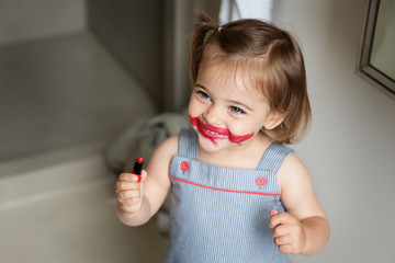 Happy little girl with smeared lipstick on face