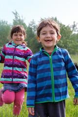 Zwei Geschwister laufen im Grünen auf der Wiese