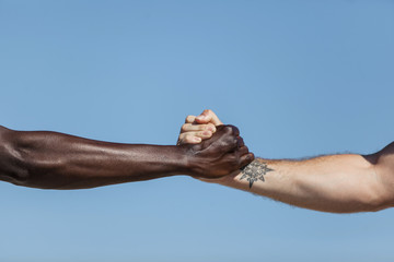 Close up of friends holding hands tightly against blue sky