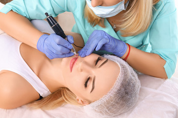 Cosmetologist making permanent makeup on woman's lips