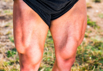 Young bodybuilder showing quads outdoors