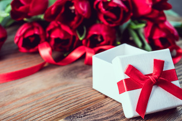 Tulips and gift box with red bow on rustic wooden background with copy space. Spring border with free space. Greeting card for Woman's Day and Mother's Day or birthday holiday.