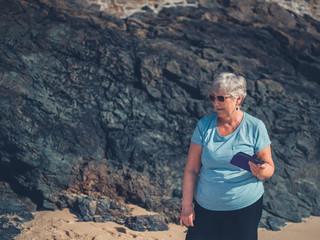Senior woman with phone on the beach