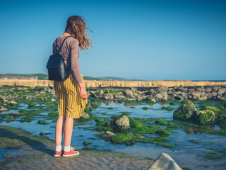 Young woman with backpack by the sea
