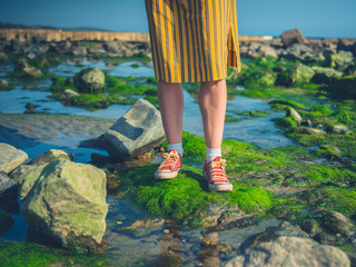 Feet and legs of woman standing on rocks by the sea