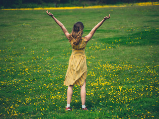 Woman raising her arms in a meadow