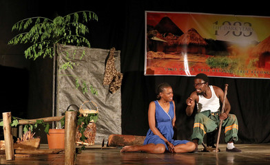 """Zimbabwean actors perform on stage in a production of """"1983 - The Dark Years"""" in Harare"""