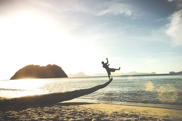 Silhouette of traveler guy on funny jump from palm - Travel wanderlust concept with man having fun at Las Cabanas beach in El Nido Palawan - Soft tilted horizon and vintage turquoise pastel filter