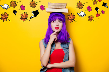 Portrait of young style hipster girl with purple hairstyle with books and leaves on yellow background
