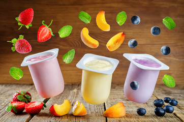 Variation of fruit yoghurts: strawberry, blueberry and peach