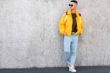 fashion guy standing near a concrete wall in yellow clothes
