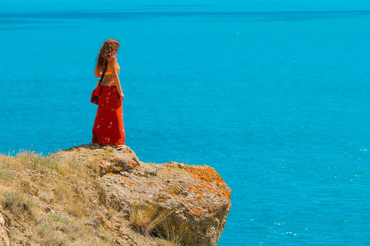 A woman is standing alone and on the edge of a cliff and looking over the blue Sea