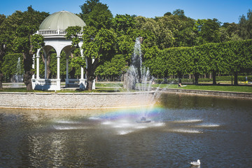 View to the pond with the fountain, rainbow appears in the water.