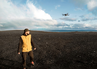 guy tourist launches quadrocopter with hands in the mountains