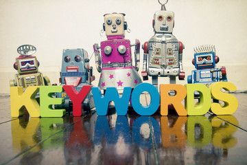 the word  KEYWORDS with wooden letters and retro toy robots  on an old wooden floor