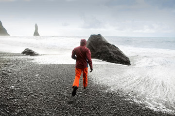 guy tourist running on the beach in Iceland, freedom concept