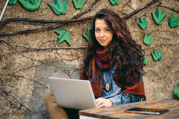 Woman using laptop and smiling while sitting in the garden.