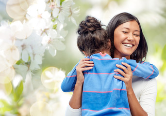family, motherhood and people concept - happy mother and daughter hugging over cherry blossom background