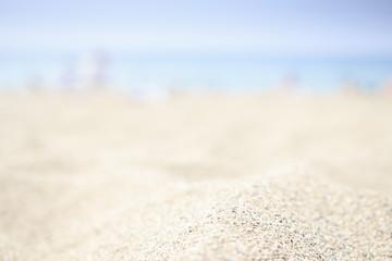 Blurred beach background with white sand, blue sea and sky on horizon. Sandy beach.