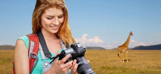 travel, tourism and photography concept - happy young woman with backpack and camera photographing over giraffe in african savannah background