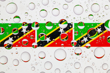 Water drops on glass and flags of Saint Kitts and Nevis