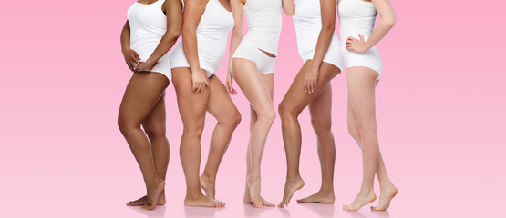 beauty, body positive and people concept - group of diverse women in white underwear over pink background