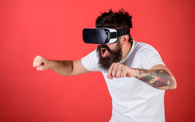Hipster on excited face driving bike on high speed in virtual reality with modern digital gadget. Man with beard in VR glasses driving motorbike, red background. Virtual driving lessons concept
