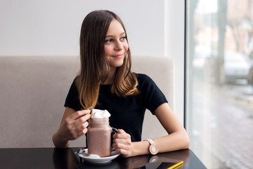 girl drinks coffee and watches video on mobile phone
