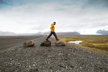 tourist jumps over rocks in Iceland