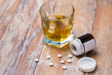 Photo sur Plexiglas Bar drug abuse, addiction and suicide concept - glass of alcohol and pills on table