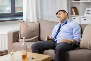 alcoholism, alcohol addiction and people concept - male alcoholic with glass of whiskey sleeping on sofa at home