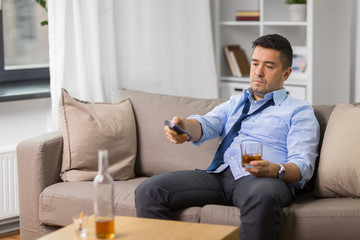 alcoholism, alcohol addiction and people concept - drunk man or alcoholic with tv remote drinking whiskey at home