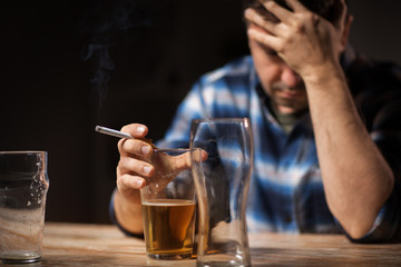 Poster Bar alcoholism, alcohol addiction and people concept - close up of male alcoholic drinking beer and smoking cigarette at night