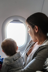 A little baby child and mother looks through the window on an airplane. Concept for traveling with children / family, vacation and holiday.