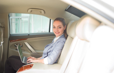 Beautiful young business woman using laptop and smiling while sitting on back seat in the car.