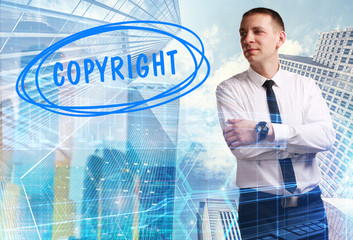 The concept of business, technology, the Internet and the network. Young businessman showing inscription: Copyright