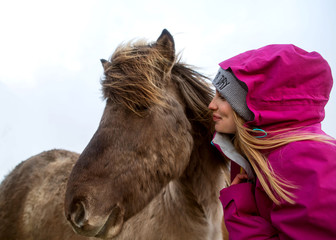 girl with a horse hugging and laughing.